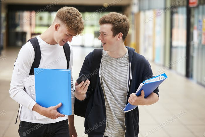 Two Male College Students Reading Text Message On Mobile Phone