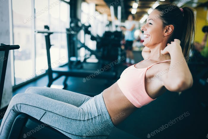 Beautiful woman doing exercises for abs in gym