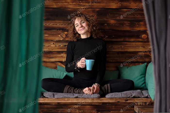 Young athletic woman is drinking tea after yoga training