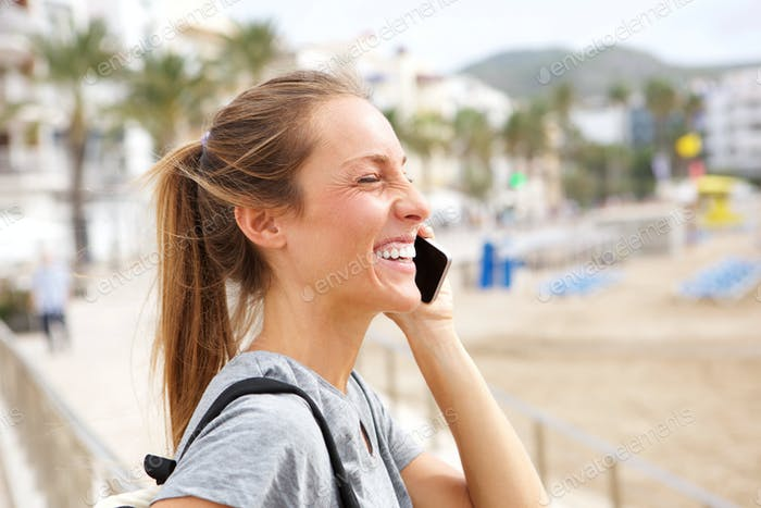 Side smiling young woman talking on mobile phone at the beach