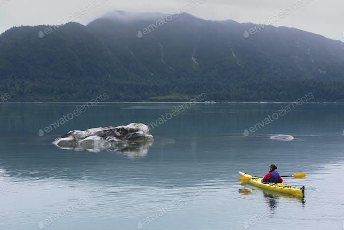 Female sea kayaker paddling pristine waters of Muir Inlet, Alaska