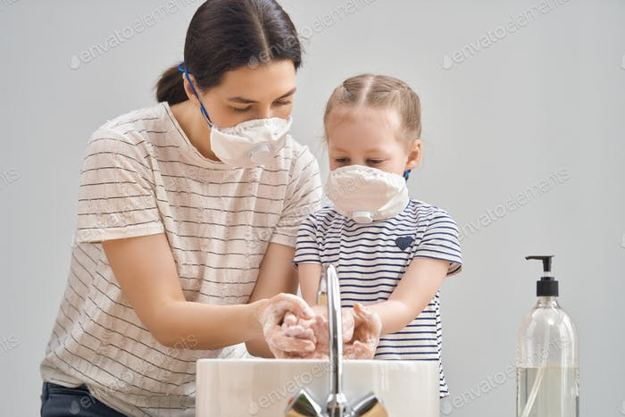 family wearing facemasks and washing hands
