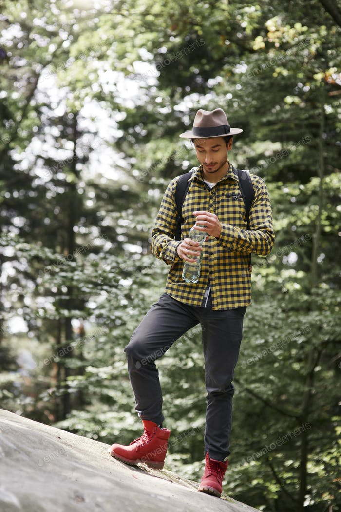 Männliche Wanderer Trinkwasser in den Bergen