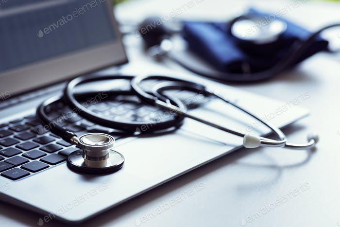 Stethoscope on laptop keyboard in doctor surgery