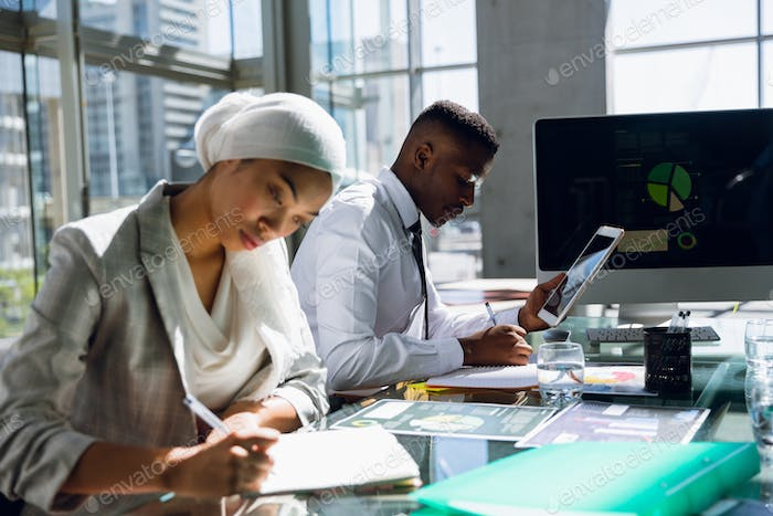 Male and females executives working together at desk