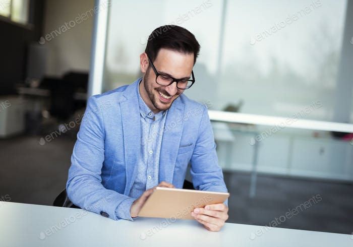 Handsome businessman using tablet pc in office