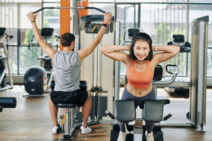 Couple exercising in gym machines