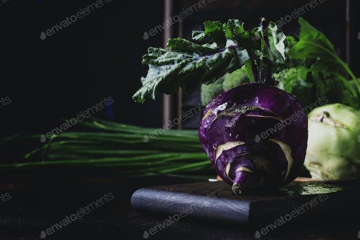 Purple organic fresh kohlrabi cabbage, summer harvest on brown kitchen table