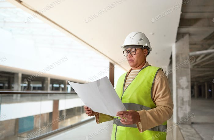 Female Engineer Inspecting Plans on Construction Site