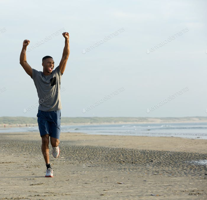 Young black man running on beach with arms raised