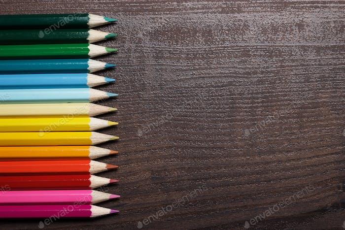 Bunte Bleistifte auf dem braunen Holztisch Hintergrund