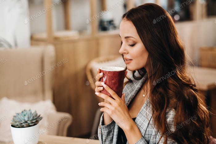 a girl drinks coffee in a coffee shop, beautiful hair of a girl