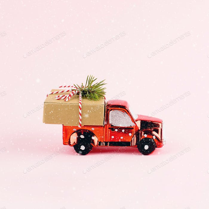Red toy car delivering Christmas or New Year gift present box on pink background.