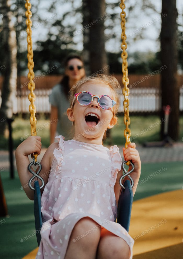 Happy Laughing child on swing in summer park. Girl in sunglasses have fun.