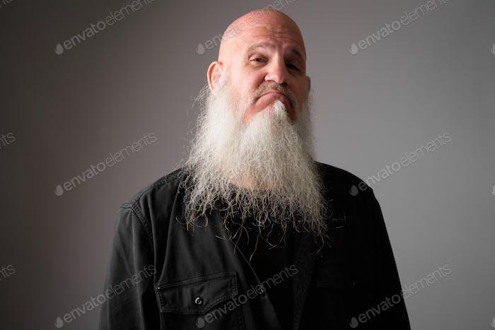 Gesicht der reifen Glatze Mann mit langen Bart machen smug Ausdruck