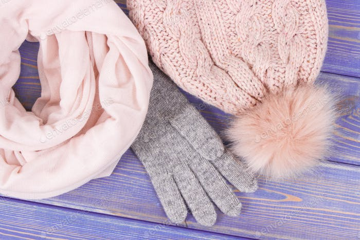 Woolen womanly gloves, cap and shawl for autumn or winter on old boards