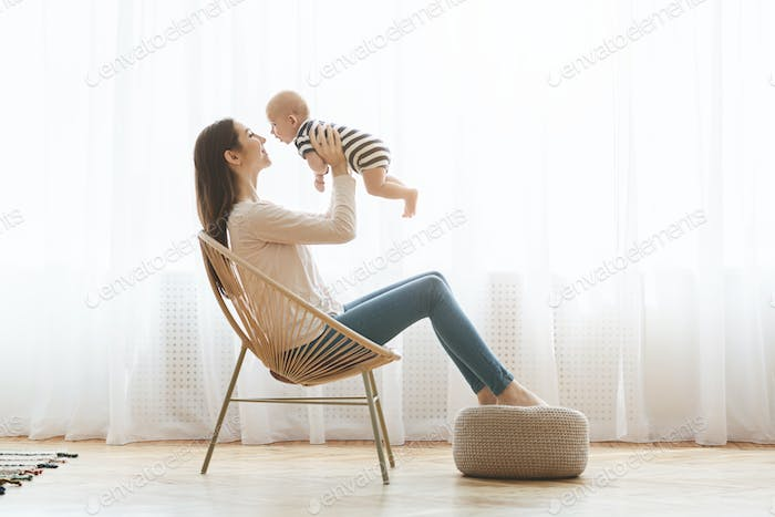 Mother sitting in chair and lifting her newborn child up
