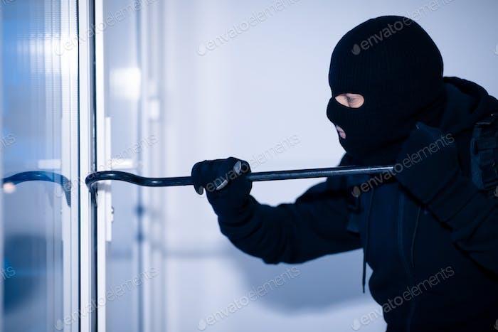 Robber in black balaclava cracking door with crowbar