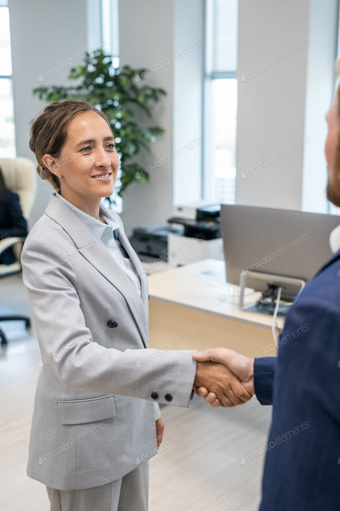 Young businesswoman looking at colleague durng handshake