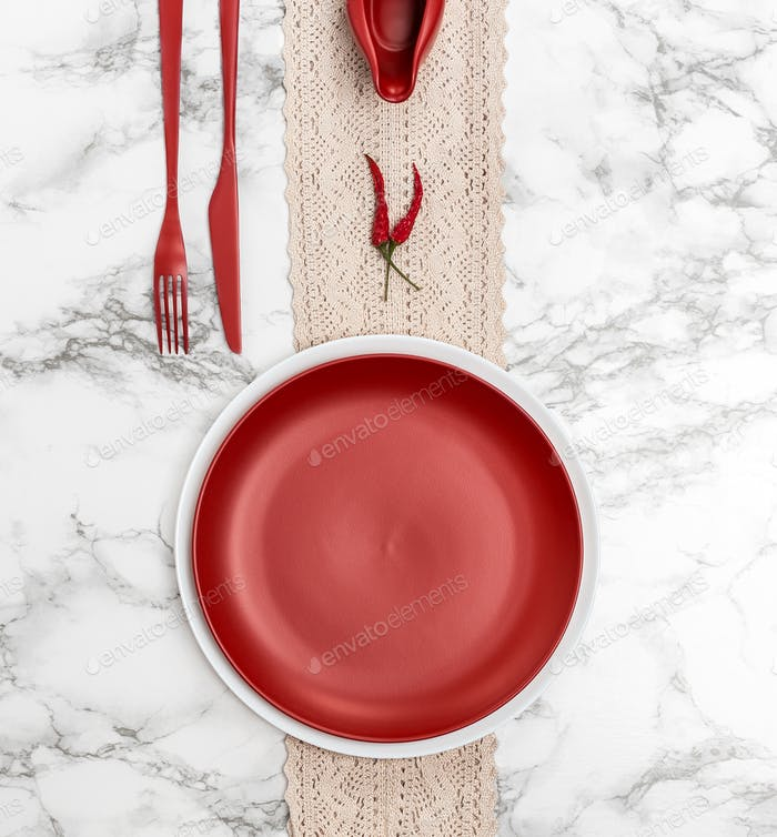 Red dishes and cutlery on the marble table.