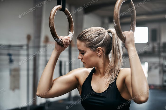 Fit young woman working out on rings at the gym