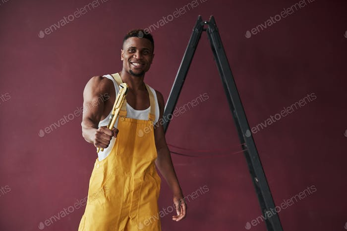 Man with strong hands. Young african american worker in the yellow uniform have some job