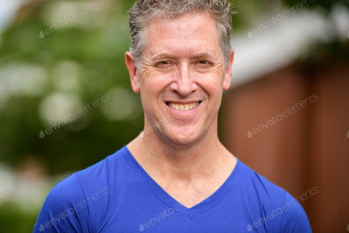 Face of happy mature man smiling in the streets outdoors