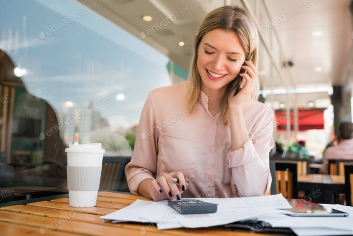 Businesswoman talking on phone while working at coffee shop.