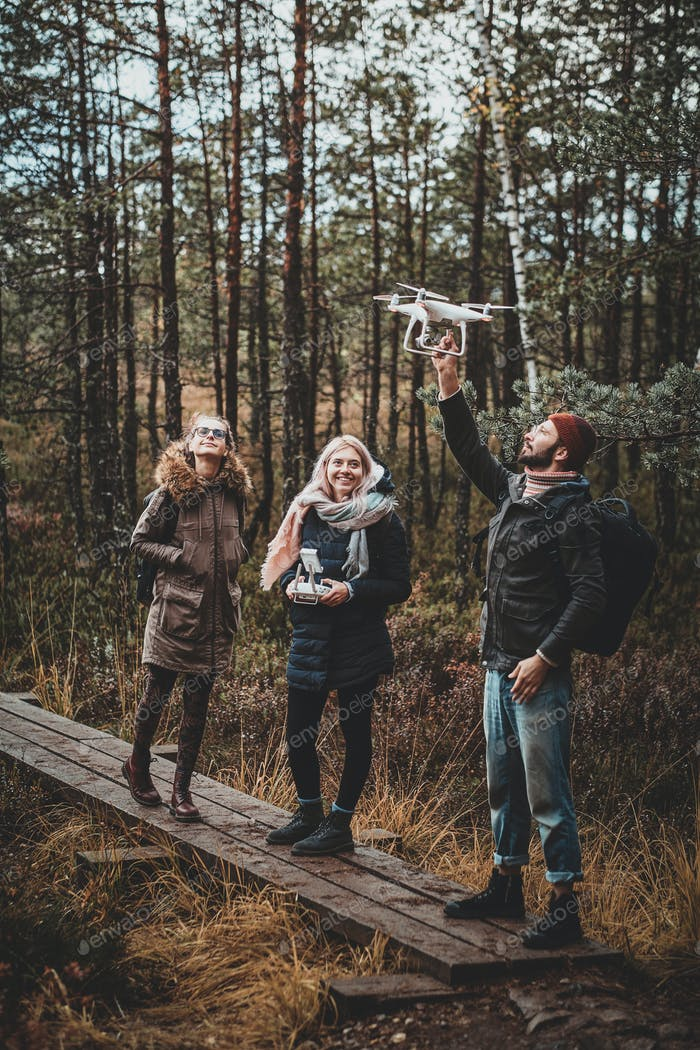 Group of friends are enjoying autumn hike in forest