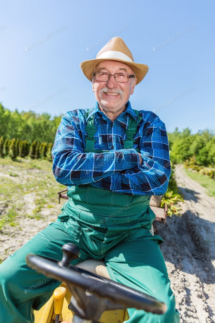 Senior man sitting proud in his tractor after cultivating his farm