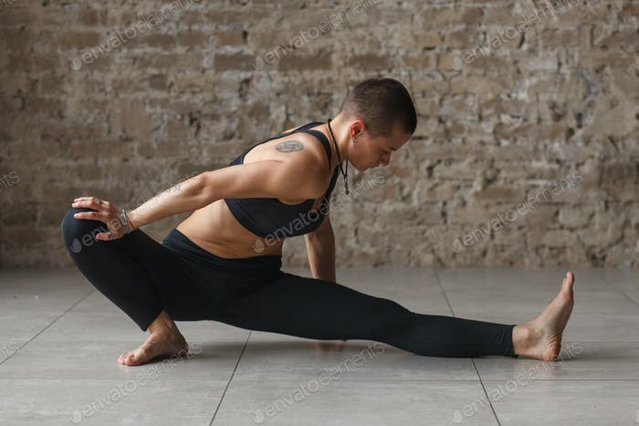 athletic woman stretching her legs alone at home
