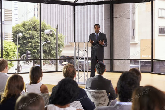 Black businessman presenting seminar gesturing to audience