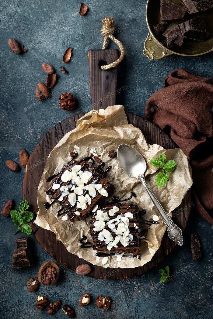 Chocolate brownie cake, dessert with nuts on dark background, directly above, flat lay