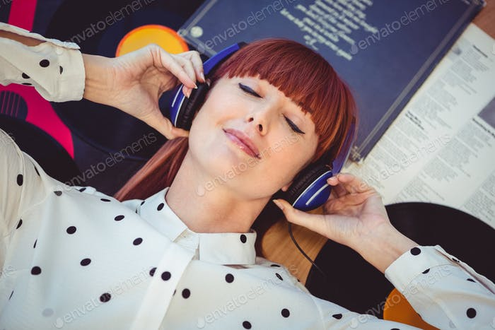 Above view of attractive hipster woman with closed eyes and headphones