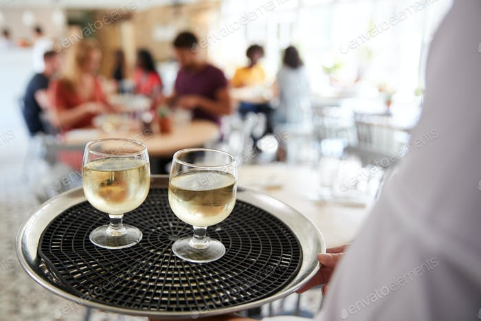 Tray with drinks carried by waiter at a restaurant, close up