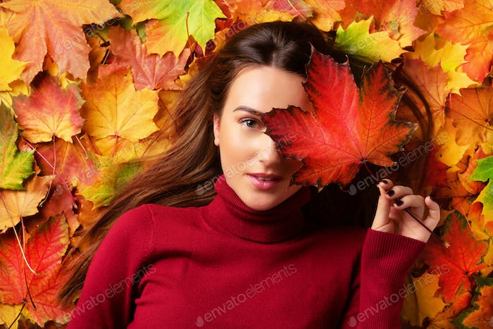 Girl holding red maple leaf in hand over colorful fallen leaves background. Gold cozy autumn concept