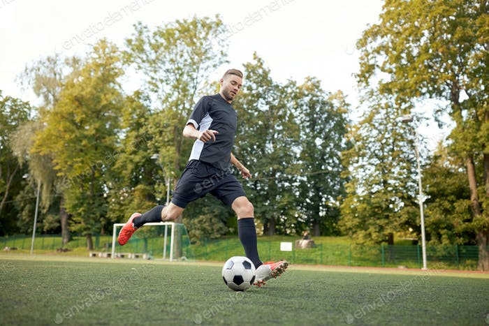 soccer player playing with ball on football field