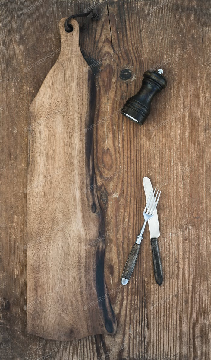 Kitchen-ware set. Old rustic serving board, knive and fork, pepperbox on a old wooden background