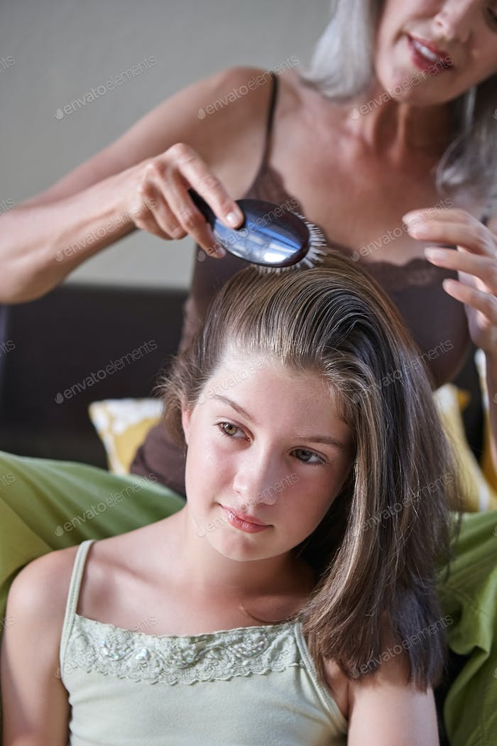 A mother brushing her teenage daughter's hair.