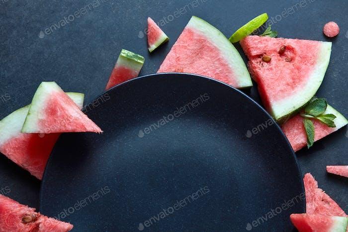 Scheiben von Wassermelone in der Nähe der Platte platziert schwarz