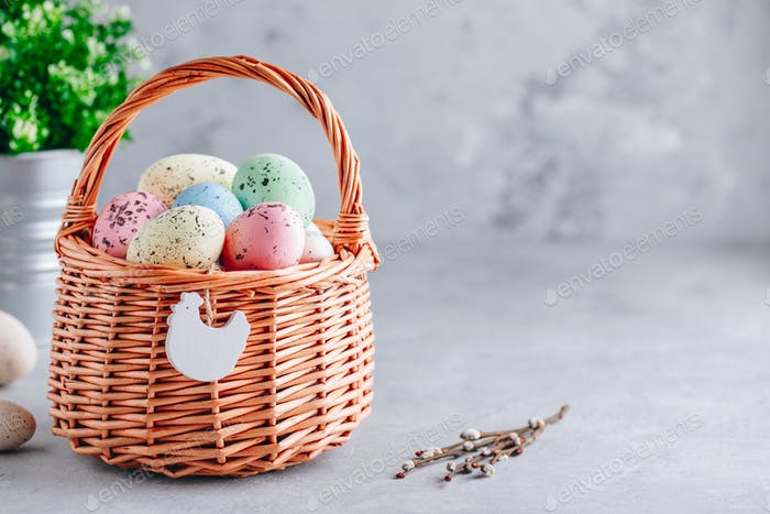 Colorful Easter eggs in the basket on gray stone concrete background
