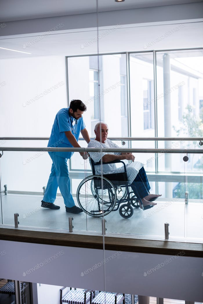 Male doctor interacting with male senior patient in the passageway