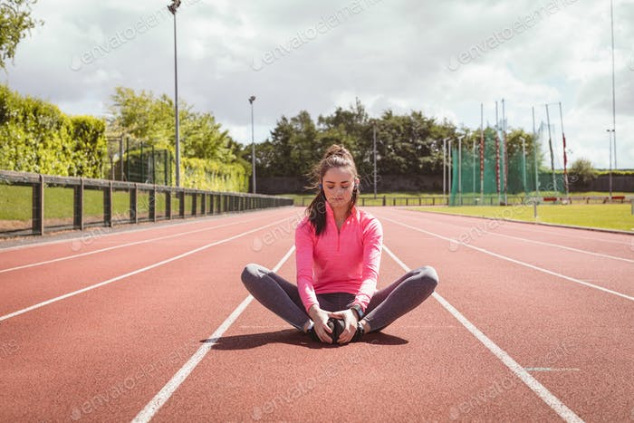 Thumbnail for Woman performing stretching exercise on a race track