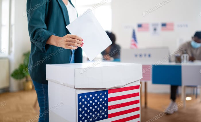 Unrecognizable woman putting her vote in the ballot box, usa and coronavirus elections