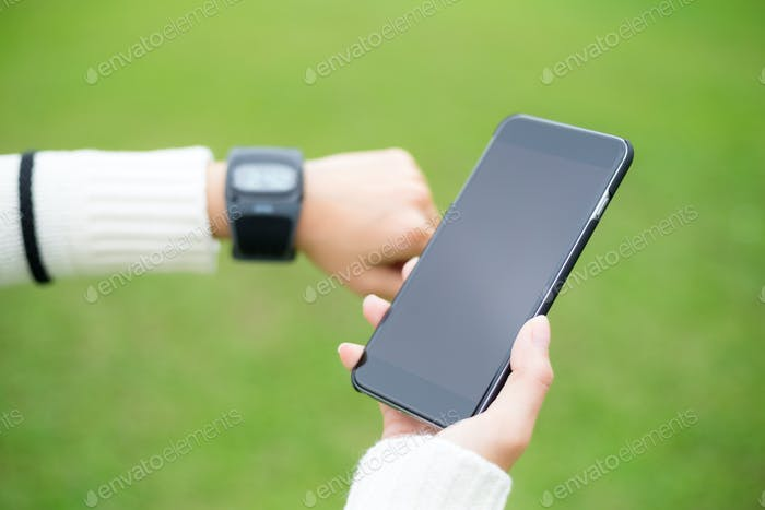 Woman with wearable watch and cellphone over green background