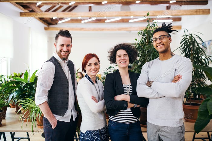 Group of young businesspeople standing in office, looking at camera