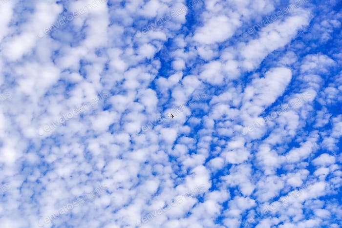 Small airplane flying on a cloudy sky background