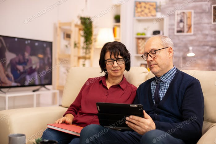 Beautiful old couple using a digital tablet to chat with their family