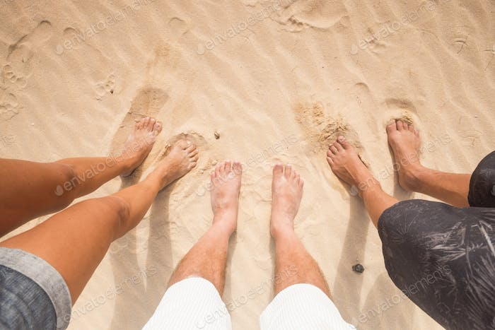 Three pair of feet in the sand