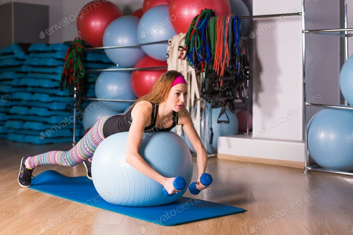 Woman with dumbbells and exercise ball in gym